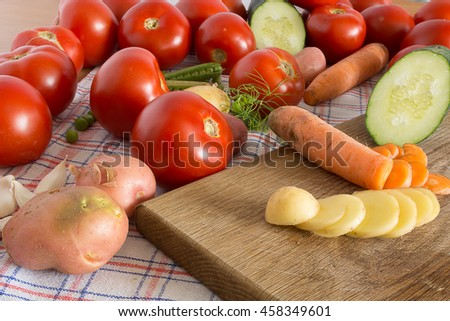 Sliced vegetables on a wooden plate in the kitchen