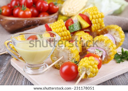 Sliced vegetables on picks on board on table close-up