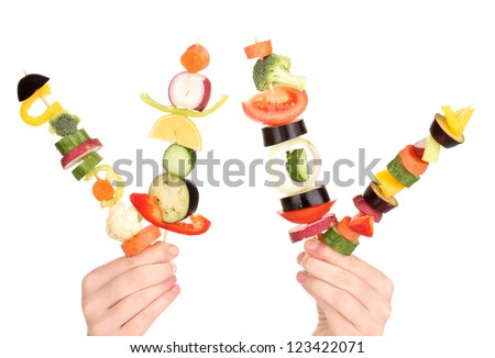 Sliced vegetables on wooden picks holding in hands isolated on white - stock photo