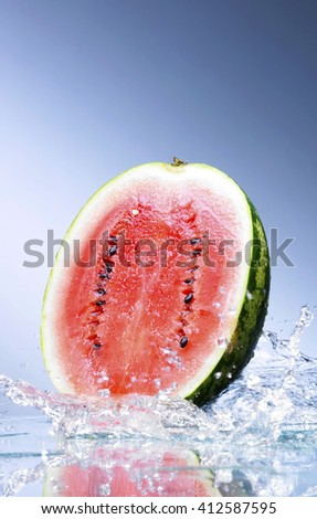Sliced Watermelon Falling into Water Splash isolated on black background - stock photo