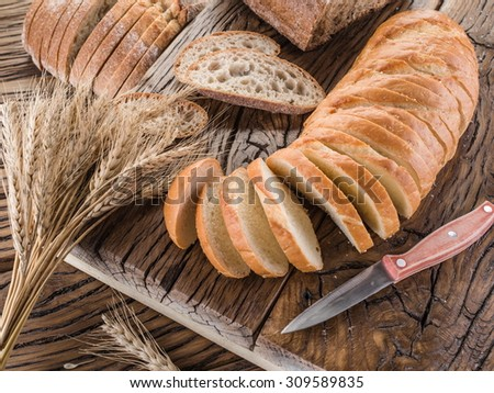 Sliced white bread on the old wooden plank. - stock photo