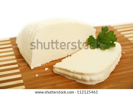 sliced white goat cheese on wooden plate - stock photo