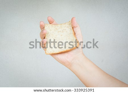 sliced whole wheat bread in human hand with gray background