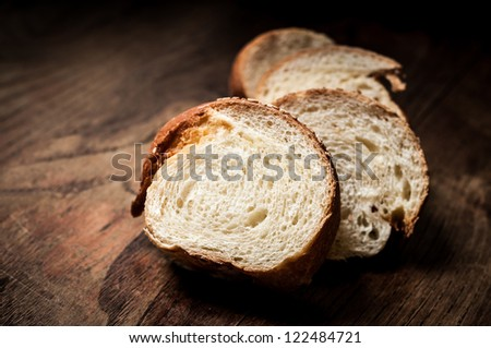 sliced wholemeal sesame bread on brown wood - stock photo
