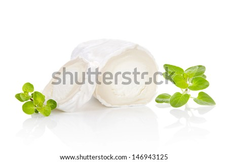 Slices goat cheese and goat cheese piece with fresh marjoram herbs isolated on white background. Culinary cheese eating. - stock photo