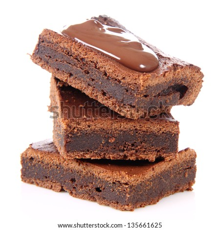 Slices of a brownie on white background covered with chocolate