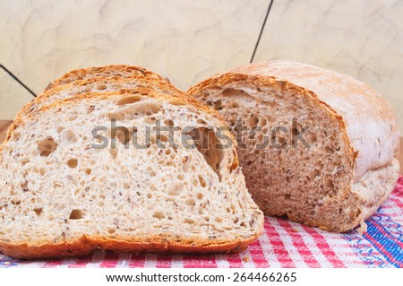 Slices of a dark bread with seeds on the table in the kitchen - stock photo
