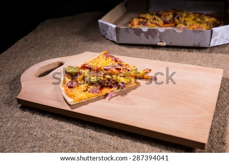 Slices of Artisinal Pizza on Wooden Cutting Board with Cardboard Take Out Box in Background on Burlap Covered Table - stock photo