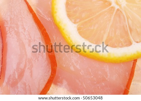 Slices of bacon and lemon as background - stock photo