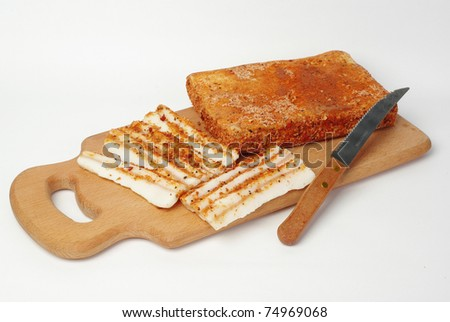 Slices of bacon on wooden board - stock photo