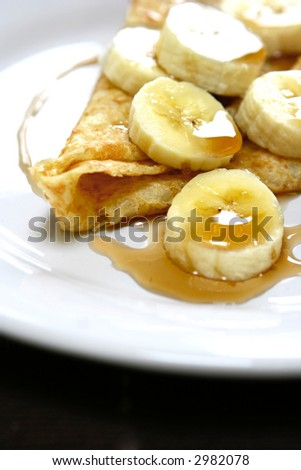 Slices of banana served with maple syrup on warm pancake with melted butter. - stock photo