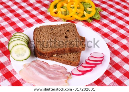 Slices of black bread, thinly sliced â??â??bacon, yellow peppers, cucumbers and radishes on the table. Cooking sandwich. Time for lunch. Breakfast. A simple recipe for a sandwich. Selective focus. - stock photo