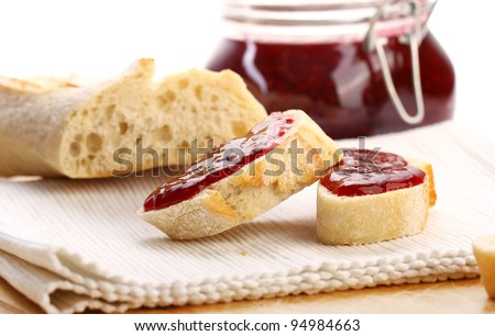 Slices of bread and raspberry jam on the table - stock photo