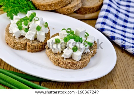 Slices of bread with feta cheese and chives on a plate, parsley, napkin on a wooden board