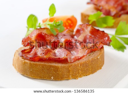 Slices of bread with fried bacon strips on white background