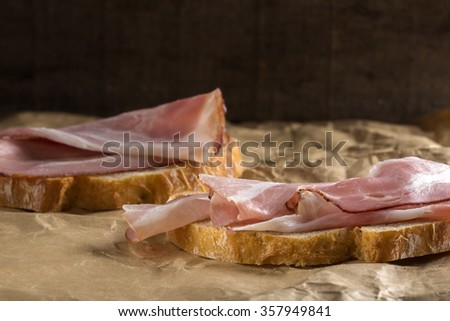 Slices of bread with ham over paper background - stock photo