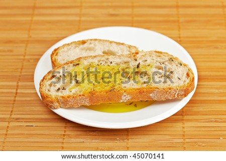 Slices of bread with olive oil on wooden background. Shallow depth of field