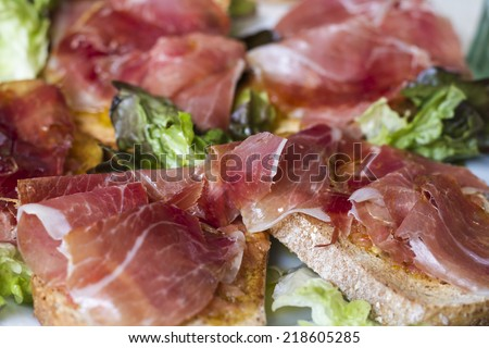 Slices of bread with spanish ham and salad - stock photo
