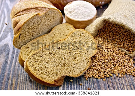 Slices of buckwheat bread, a bag of buckwheat, buckwheat flour in a bowl on a wooden boards background - stock photo