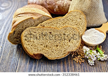 Slices of buckwheat bread, a bag of buckwheat, buckwheat flour in a spoon, flower buckwheat on a background of wooden planks - stock photo