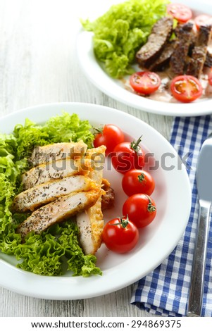 Slices of chicken fillet with spices and cherry tomato on table close up