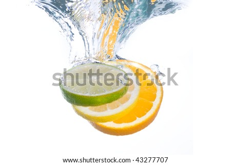 Slices of citrus fruit falling into clear water