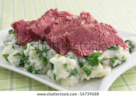 Slices of corned beef on top of colcannon (mashed potatoes with kale). - stock photo