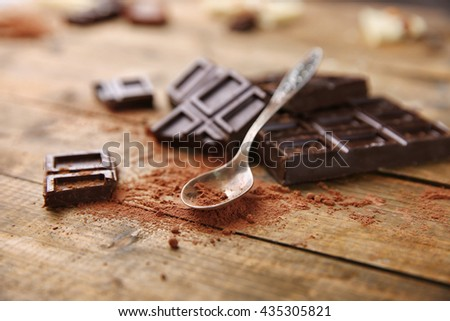 Slices of dark chocolate and spoon with cocoa powder on table - stock photo