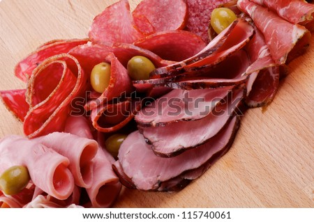Slices of Delicatessen with Ham, Pepperoni, Chorizo and Olives closeup on Cutting Board - stock photo
