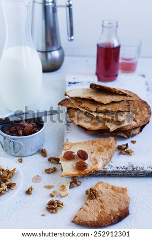 Slices of delicious homemade crispy tortillas sifted with grape jam and walnuts, arranged on vintage wooden table. Taken on a white background. White country style kitchen. Homemade food.    - stock photo