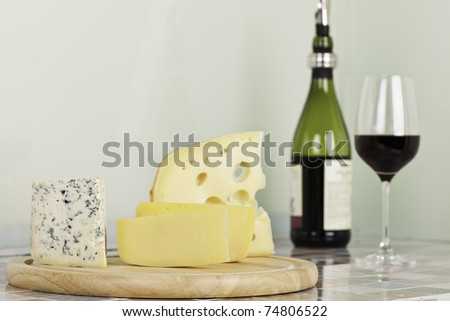 Slices of different kinds of cheese, red wine . A shot horizontal, focus in the shot foreground. - stock photo
