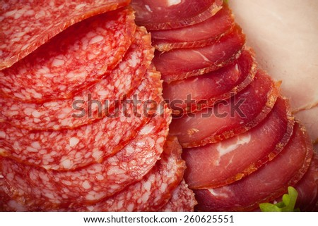 Slices of different types of sausages and salad leaf. Toned. - stock photo