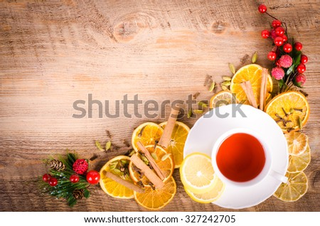 Slices of dried orange, lemon, cinnamon, cloves, cardamom, pine cone and cup of tea. Christmas and New Year decoration. Free space for text. - stock photo