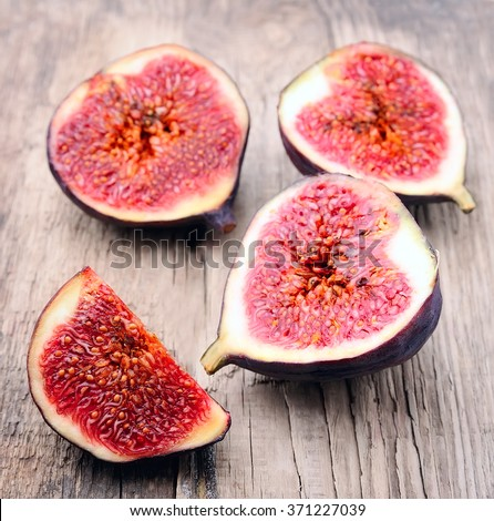 Slices of figs on wooden texture - stock photo