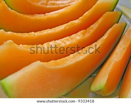Slices of fresh appetizing orange cantaloupe on a dish - stock photo