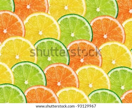 Slices of fresh citrus fruits isolated on white background - stock photo