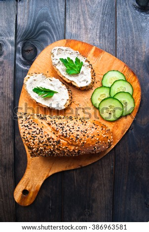 Slices of fresh cucumber, baguette with sesame and sandwich with cream cheese and parsley on wooden cutting board - stock photo