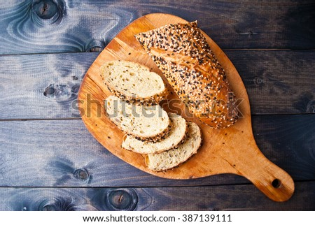 Slices of fresh homemade baguette served on beige cutting board. Top view. Food background - stock photo