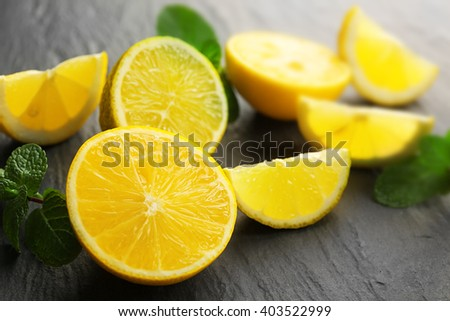 Slices of fresh lemon and lime on black textured background - stock photo