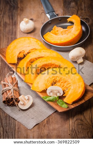 Slices of fresh pumpkin on wooden background, selective focus - stock photo