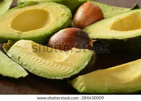 Slices of fresh ripe avocado on a dark wooden table - stock photo