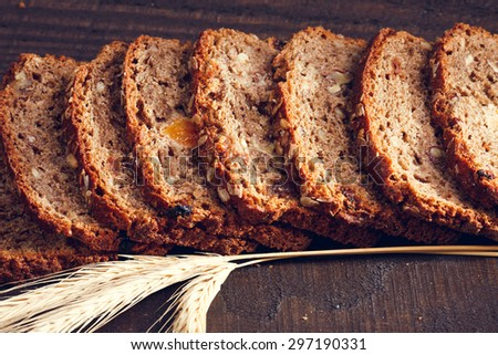 Slices of freshly baked whole grain bread with spikelets of wheat on the dark wooden boards, close up - stock photo