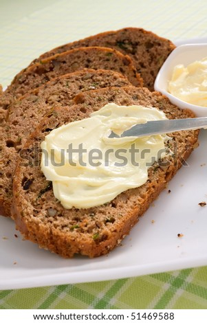 Slices of freshly baked zucchini bread served with butter.