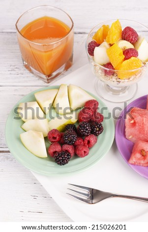 Slices of fruits with berries and muesli on wooden table