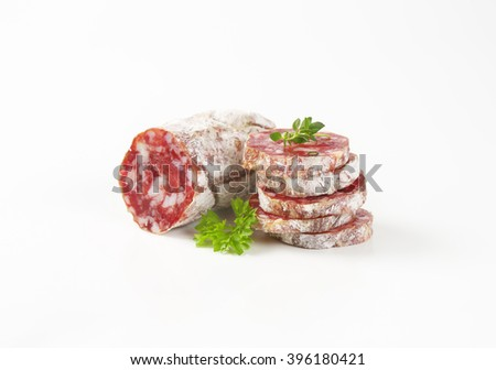 Slices of fuet sausage on white background