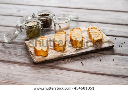 Slices of grilled baguette. Jar with bay leaves. Best bread for tasty sandwiches. Set of essential spices. - stock photo