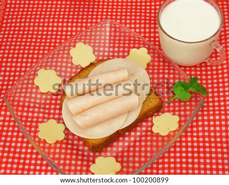 Slices of ham and cheese in flower shape and milk - stock photo