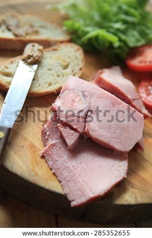 Slices of ham, lettuce, tomato, bread and a deli mustard - stock photo