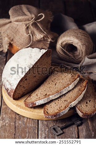 Slices of homemade bread on rustic wooden background - stock photo
