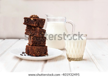 slices of homemade chocolate brownie with walnuts stacked pyramid and a glass of milk for breakfast, low key, selective focus - stock photo